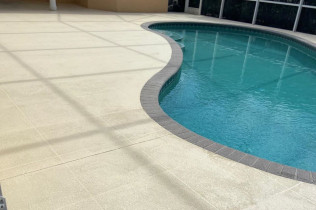 A large home with a large pool and newly resurfaced pool deck